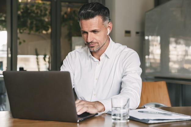 Foto di un uomo d'affari europeo anni '30 che indossa una camicia bianca e auricolari wireless seduto al tavolo in ufficio e lavora al computer portatile