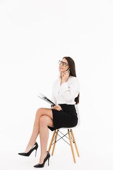 Foto di una donna d'affari europea lavoratrice vestita in abiti formali che parla sullo smartphone mentre è seduta su una sedia da ufficio isolata su un muro bianco