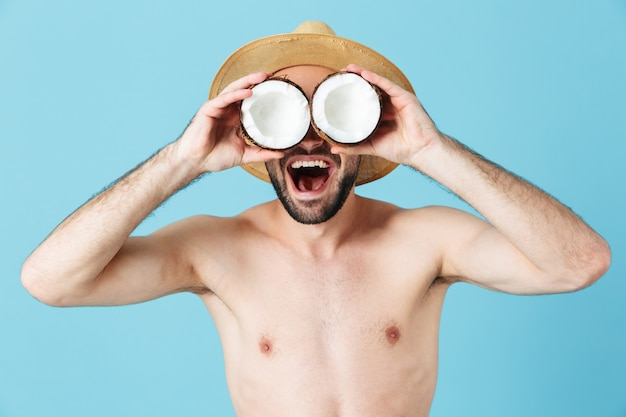 Foto di un turista europeo a torso nudo che indossa un cappello di paglia che sorride mentre tiene in mano due parti di cocco isolate su blu