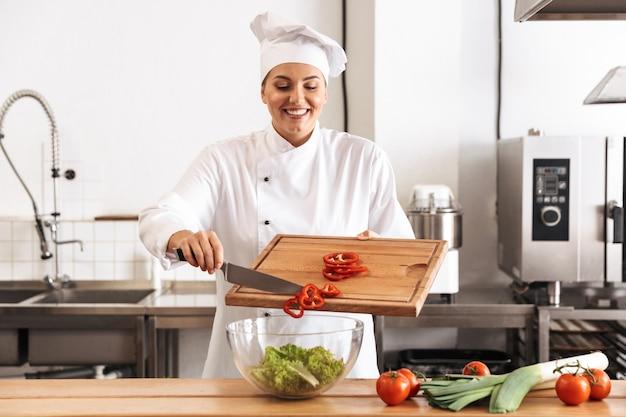 Foto del cuoco unico europeo della donna che indossa l'uniforme bianca che fa insalata con le verdure fresche, in cucina al ristorante