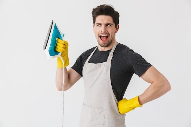 Foto di un giovane europeo che indossa guanti di gomma gialli per la protezione delle mani che sorride e tiene il ferro mentre pulisce la casa isolata su bianco