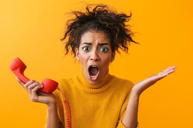 Foto della donna afroamericana eccitata con l'acconciatura afro che grida e che tiene il microtelefono rosso, isolato