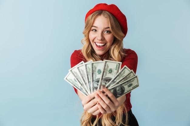 Foto della donna bionda eccitata 20s che indossa il berretto rosso che tiene il mazzo di banconote dei soldi isolate