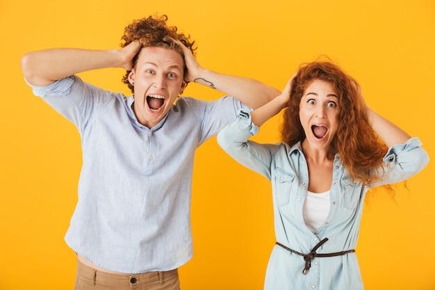 Foto di coppia eccitata uomo e donna in abiti di base urlando e afferrando le teste, isolate su sfondo giallo