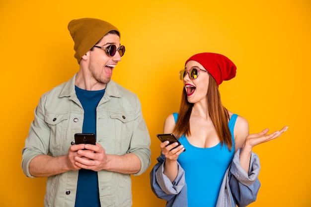 Foto di due persone eccitate e pazze, studenti, uomo, ragazzo, usare, smart blogging, social network, indossare, berretto, camicia, denim, jeans, giacca, isolato, sopra, brillante, brillantezza, colore, fondo