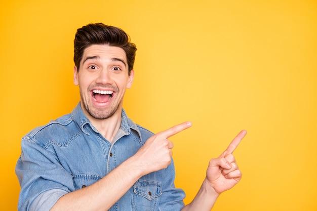 Foto di eccitato estatico uomo felicissimo che grida indicando nello spazio vuoto alle vendite con stupore sul viso isolato vivido muro di colore