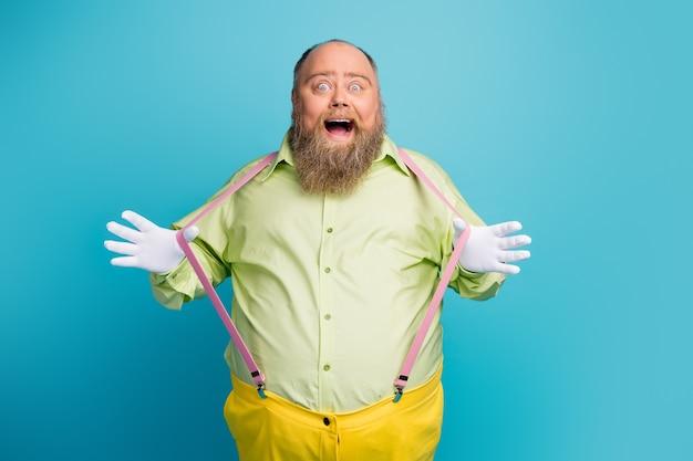 Foto dell'uomo grasso eccitato che tira le bretelle su priorità bassa blu