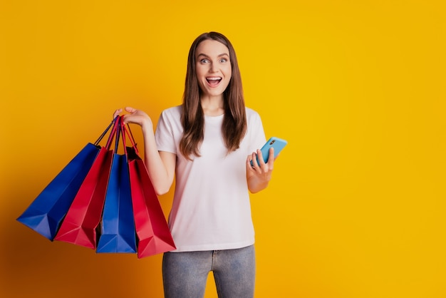 Foto di una donna eccitata che fa affari mentre chiacchiera al telefono indossa una maglietta bianca in posa su sfondo giallo