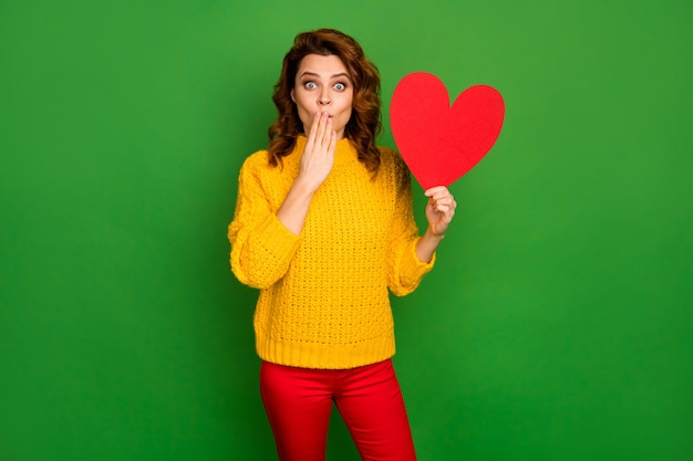 Foto di signora eccitata tenere la carta a forma di cuore cartolina nascondere la bocca non credere bel ragazzo ha invitato la sua data indossare maglione lavorato a maglia giallo pantaloni rossi isolato parete di colore verde Foto Premium