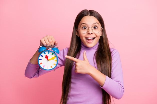 Foto di una ragazzina eccitata che punta l'orologio con il dito indice indossa un maglione viola isolato su uno sfondo di colore pastello