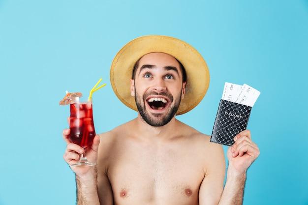 Foto di un eccitato turista a torso nudo che indossa un cappello di paglia che sorride mentre tiene in mano un cocktail e biglietti di viaggio con passaporto isolato