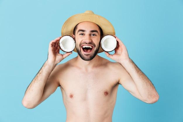Foto di un turista eccitato a torso nudo che indossa un cappello di paglia che sorride mentre tiene in mano due parti di cocco isolate sopra il blu