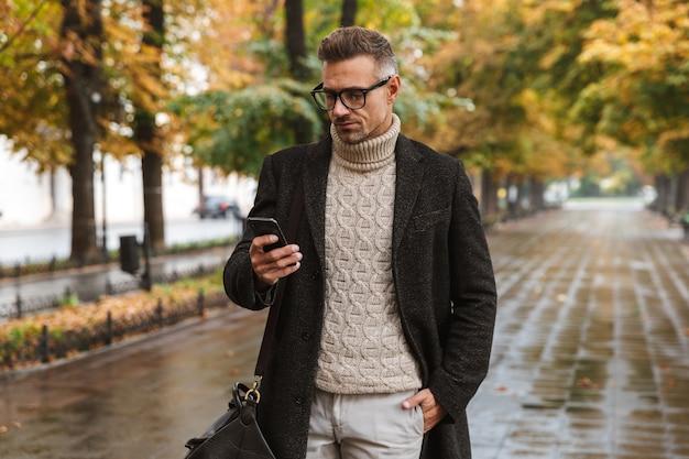 Foto di un uomo macho di moda anni '30 che indossa abiti caldi che cammina all'aperto attraverso il parco in autunno e utilizza il telefono cellulare