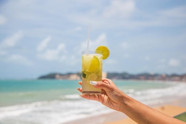 Foto della mano femminile che tiene un drink con l'oceano sullo sfondo. concetto di vacanza