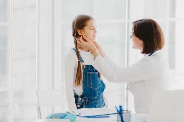 La foto della pediatra femminile esamina la gola del bambino, essendo pediatra esperto professionista