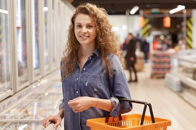 Foto di una donna con i capelli ricci e un aspetto attraente, detiene il carrello, acquista i prodotti in un supermercato, cerca i prodotti necessari nella drogheria.