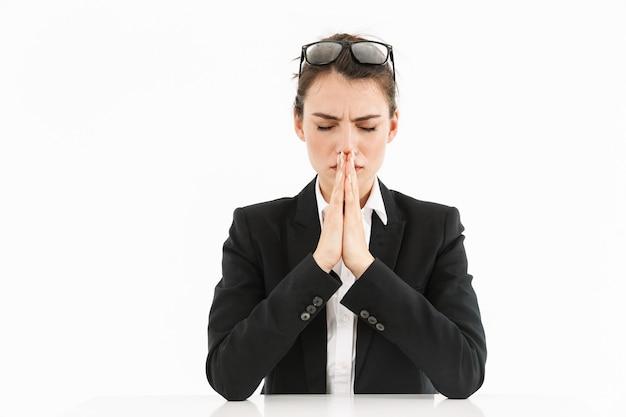 Foto di una donna d'affari lavoratrice concentrata vestita in abiti formali che tiene i palmi uniti per pregare mentre lavora in ufficio isolato su un muro bianco