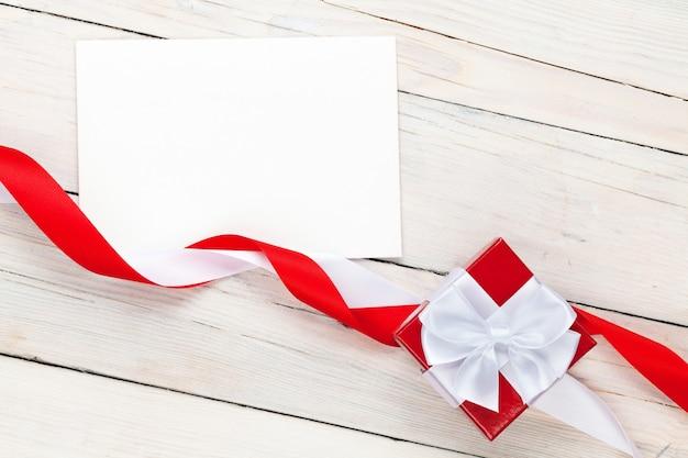 Carta cornice per foto e confezione regalo con nastro su sfondo tavolo in legno