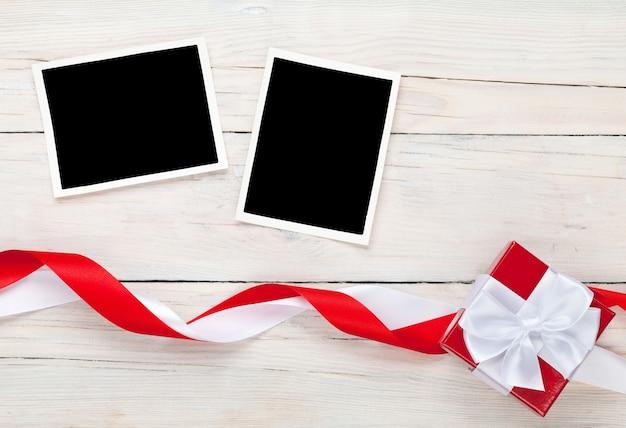 Carte portafoto e confezione regalo con nastro su sfondo tavolo in legno