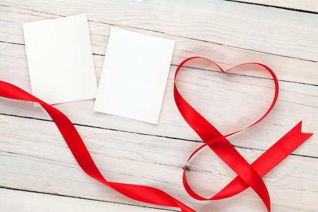 Carte portafoto con nastro a forma di cuore di san valentino su sfondo tavolo in legno