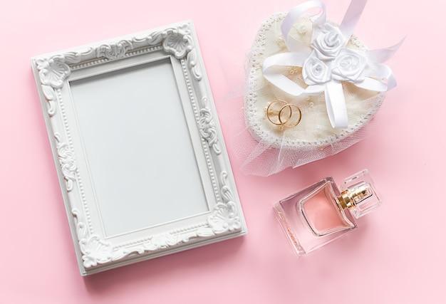 Cornice per foto e anelli d'oro sulla bottiglia bianca del cofanetto di profumo per l'anniversario di matrimonio