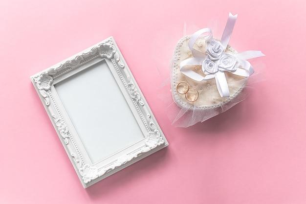 Cornice per foto e anelli d'oro sul cofanetto bianco per anniversario di matrimonio su sfondo rosa. concetto di amore