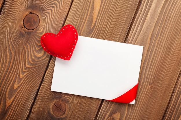 Cornice per foto o biglietto di auguri e cuore giocattolo di san valentino fatto a mano su sfondo di legno bianco