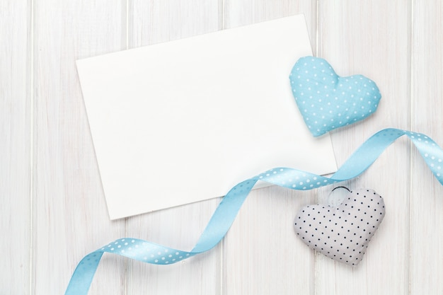 Cornice per foto o biglietto di auguri e cuori giocattolo di san valentino fatti a mano su sfondo di legno bianco