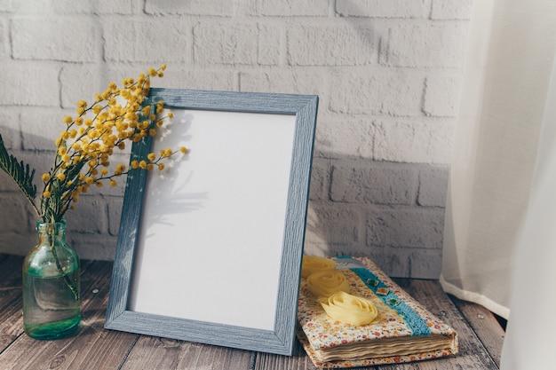 Portafoto e bottiglietta con fiori di mimosa su un muro di mattoni