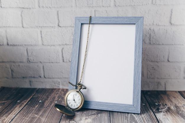 Cornice per foto con orologio rotondo vintage sul muro di mattoni