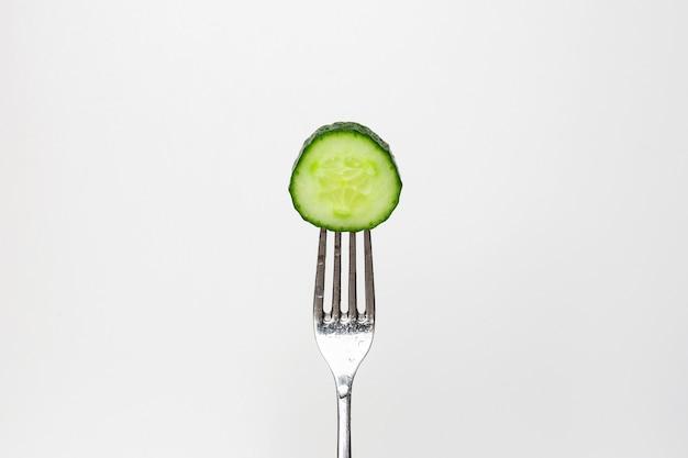 Foto di un cetriolo fresco su una forcella isolata su uno sfondo bianco