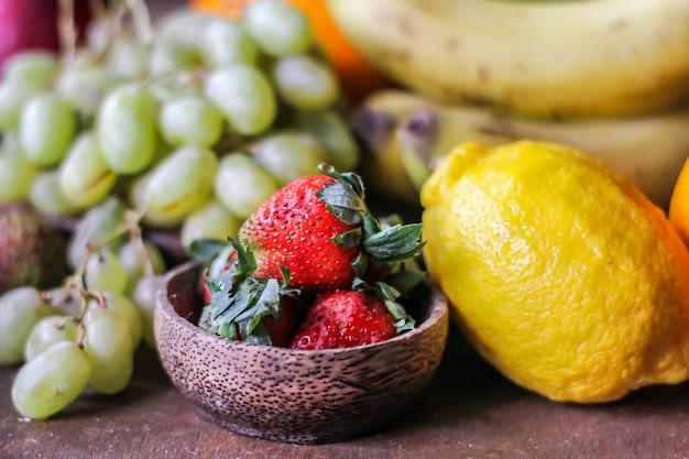 Foto delle fragole fresche con la foglia della fragola su fondo grigio rustico. un mazzo di fragole mature sulla tavola con la banana del kiwi dell'uva di limone. copia spazio. cibo organico. cibo chiaro