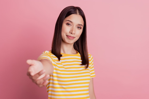 La foto della mano tesa della signora genuina e accogliente invita la stretta di mano su sfondo rosa