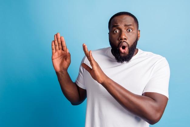 Foto di un uomo africano spaventato che gesticola con le palme di smettere di indossare una maglietta bianca su sfondo blu