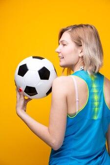 Foto dal retro della bionda con pallone da calcio su sfondo giallo in studio