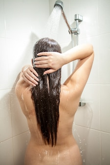 Foto dal retro di una donna sexy con i capelli lunghi che fa la doccia