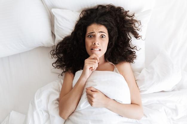 Foto dall'alto di una giovane donna confusa di 20 anni con i capelli ricci scuri che tocca il mento e sdraiata nel letto bianco con tristi emozioni