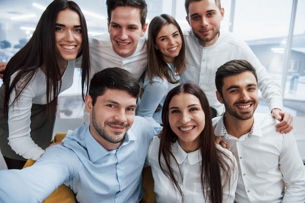 Foto dal telefono. giovane gruppo che fa selfie in vestiti classici nell'ufficio illuminato buono moderno