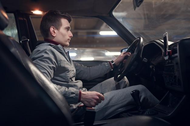 Foto dal lato del giovane seduto in macchina