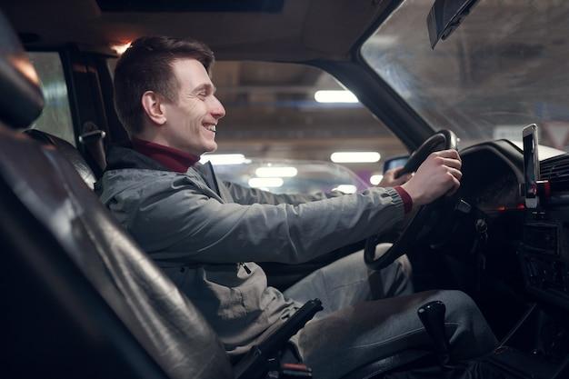Foto dal lato di un giovane uomo sorridente seduto in macchina