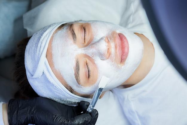Una foto dall'alto del volto di una donna su cui un cosmetologo applica gommage peeling