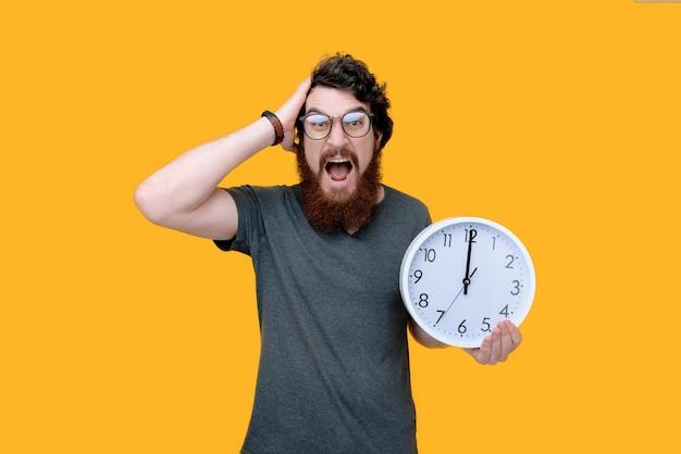 Foto del tipo barbuto frustrato, tenendo un orologio e su giallo