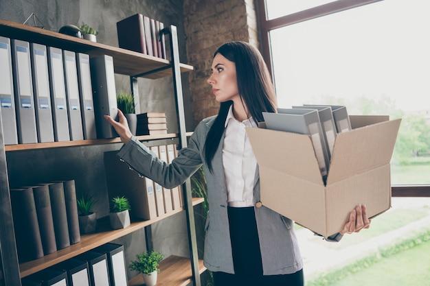 Foto di una ragazza frustrata titolare di una start-up che perde azienda in bancarotta raccoglie scaffali documenti archivi statistiche tenere scatola di cartone indossare giacca giacca blazer nella postazione di lavoro