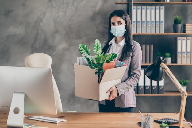 Foto di frustrata triste ragazza rappresentativa azienda in bancarotta riduzione del personale perde lavoro tenere scatola di cartone indossare tuta blazer giacca maschera medica nella postazione di lavoro