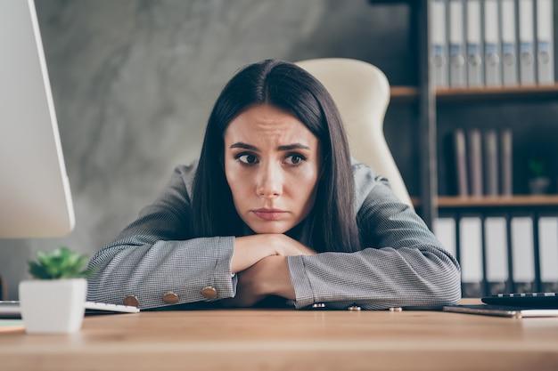 Foto di frustrata stressata ragazza depressa agente amministratore delegato lavoro remoto sedersi tavolo scrivania preoccuparsi per la sua occupazione perdita di lavoro indossare abito in moderno ufficio loft
