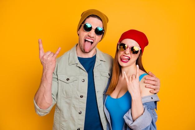 Foto di funky pazza signora ragazzo giovane coppia concerto rock tempo libero insieme fresca gioventù che mostra le corna bastone lingua indossare abiti estivi casuali isolato sfondo di colore giallo brillante