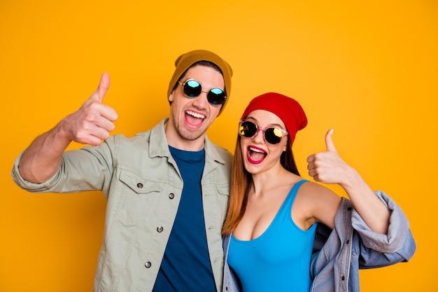 Foto di funky pazza signora ragazzo giovane coppia insieme fresca gioventù alzare le dita del pollice su buon umore per il tempo libero indossare abiti estivi casuali isolato sfondo di colore giallo brillante