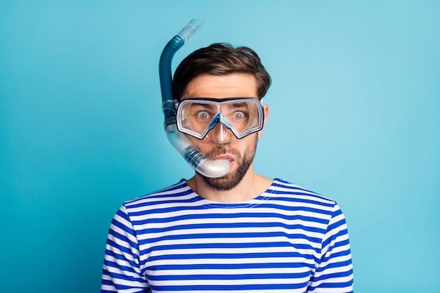 Foto di funky emotivo bel ragazzo immersioni turistiche maschera subacquea vedere pesci colorati coralli tubo di respirazione galleggiante camicia marinaio a strisce di usura profonda isolato colore blu