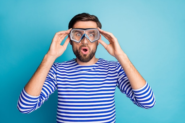 La foto di funky eccitato turista bello ragazzo prima volta che prova a fare immersioni subacquee maschera vedere coralli di pesci colorati indossare camicia da marinaio a strisce isolato colore blu