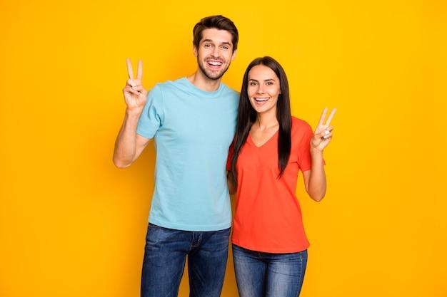 Foto di funky due persone coppia ragazzo e signora che mostra i simboli del segno di v saluto gli amici sulla festa di raccolta indossare jeans casual blu arancione t-shirt isolato su muro di colore giallo